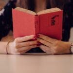 Dame læser i en rød bog med et flot ur på