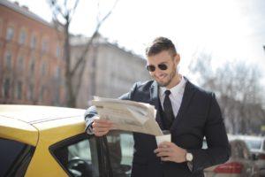 Mand går rundt og læser avis