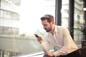 Mand i hvid skjorte kigger på sin telefon